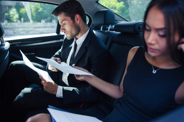 Businesswoman and businessman reading papers on back seat in car