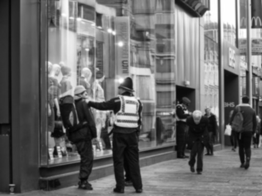 A blurred image of a man under arrest as another man, bent double with age, walks past.