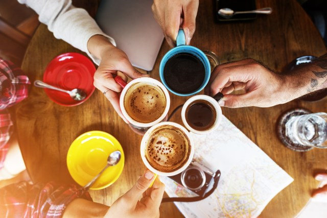 Image from above of people holding coffee cups