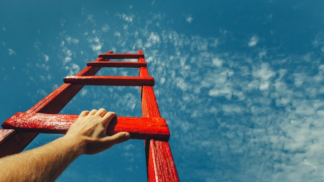 Image of a red ladder reaching toward a blue sky (re: Donald Trump border wall)