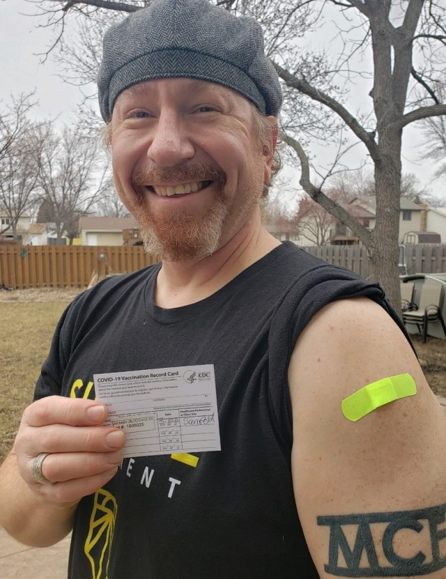 Martin C. Fredricks IV shows off COVID-19 vaccination Band-Aid and record card