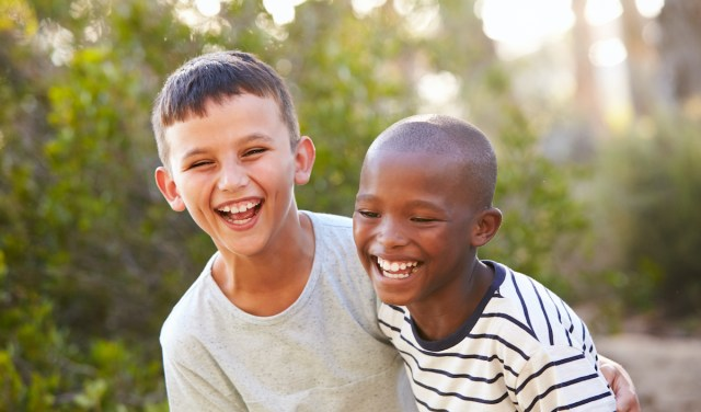 White and black boy, best friends, laughing and embracing outdoors.