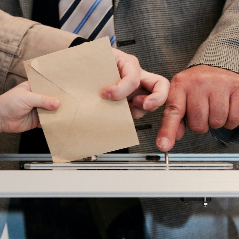 Image of a ballot being deposited in a box