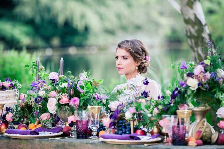 Bride sat at a table full of wedding flowers