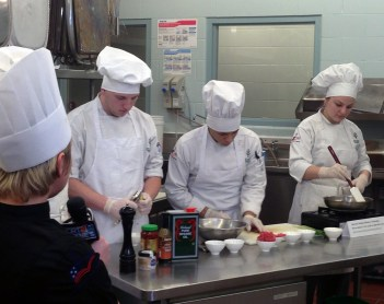 Hospitality administration instructor Sarah Hughes, far left, describes a dish cooked by students Keli Ralston, Juanito Gaona, and Kelsey Thomas.