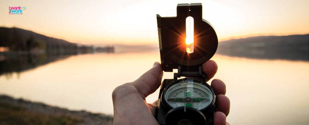 millennial career path work experience holding a compass infront of lake at sunset