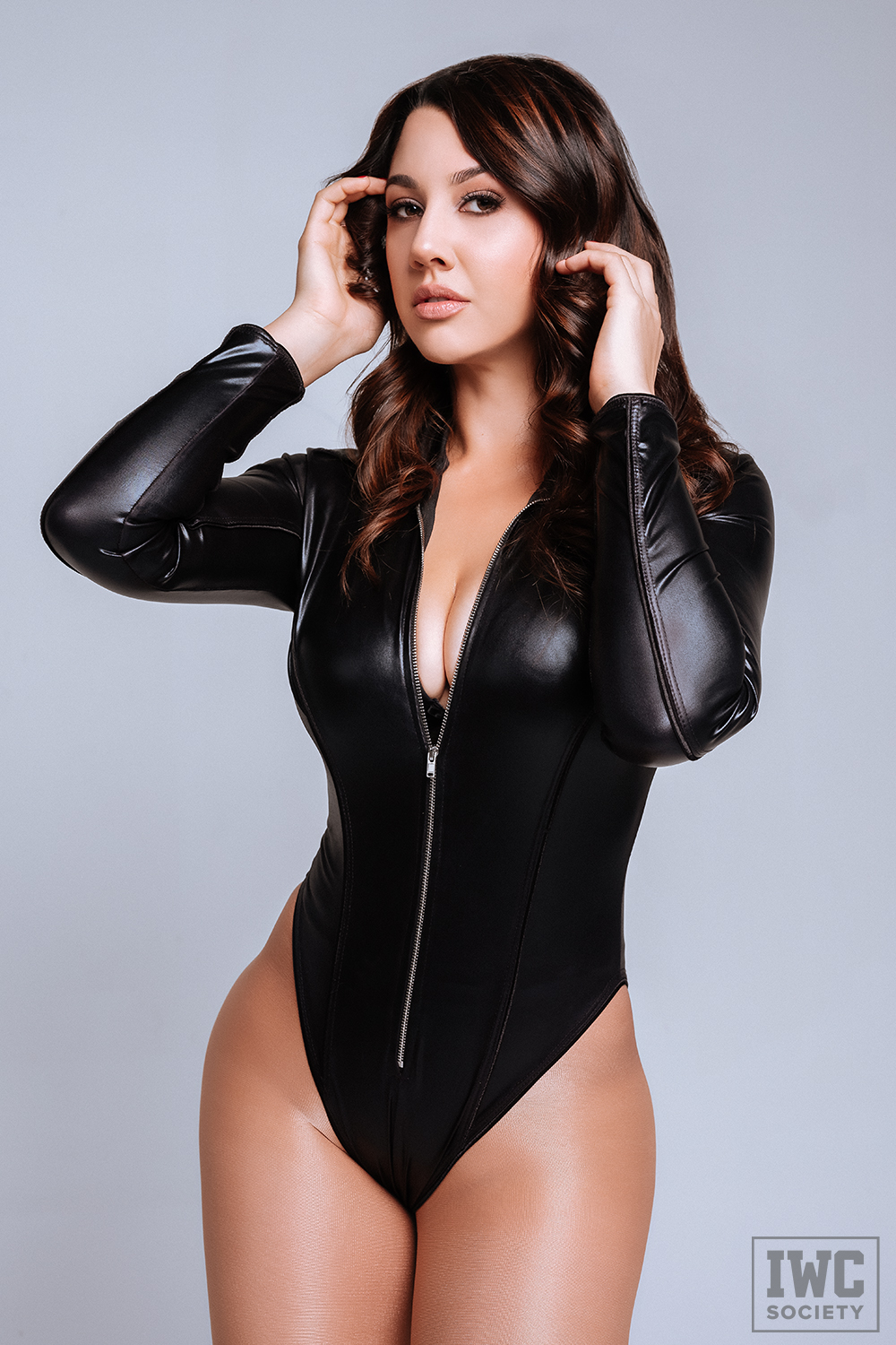 brunette domme wearing a wet look black bodysuit
