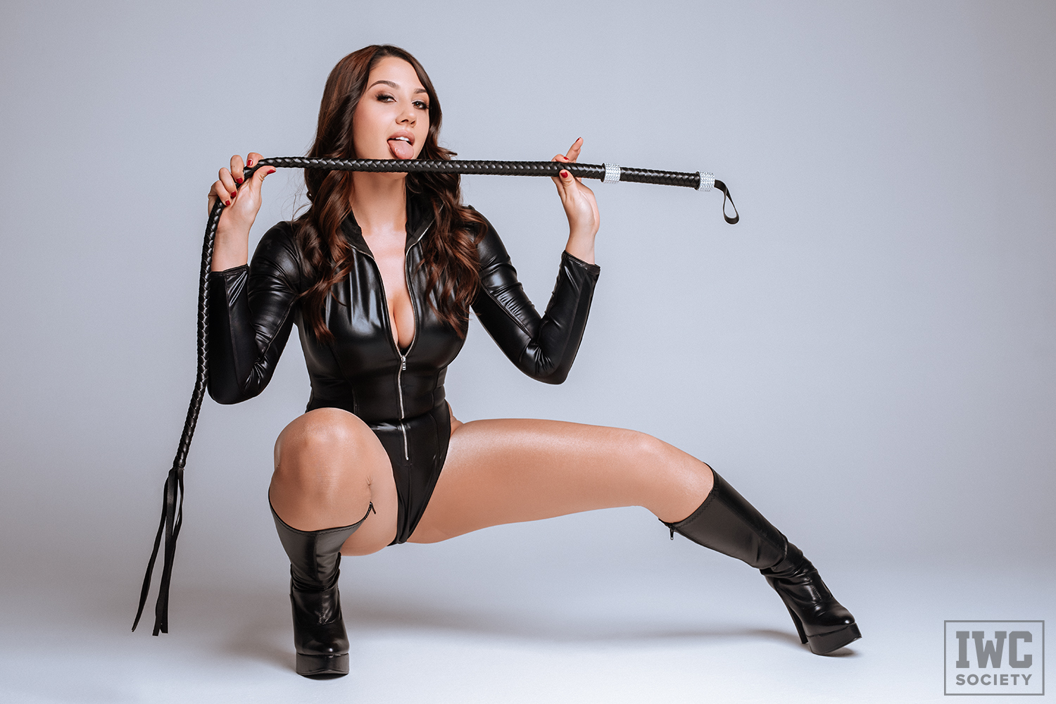 financial domme Ceara Lynch in black boots with a whip