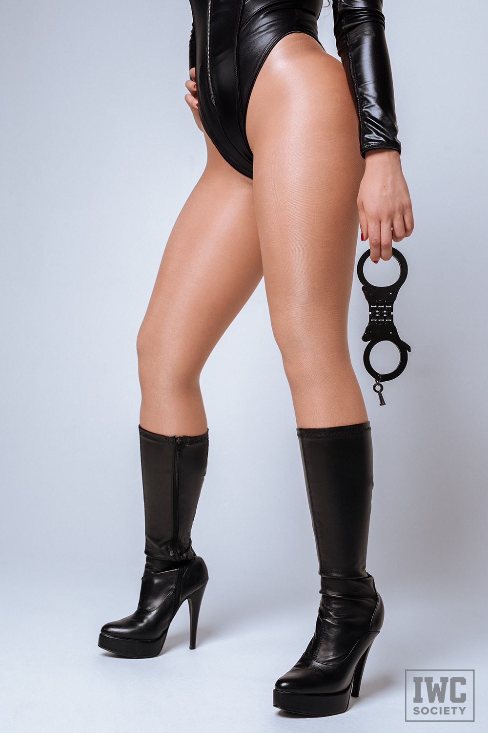 femdom woman's legs in black boots and holding handcuffs