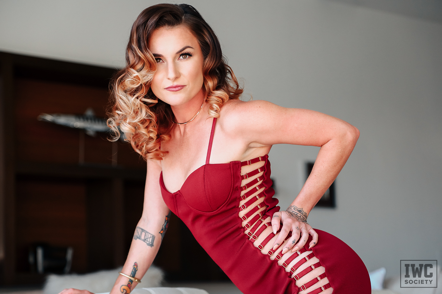 Findomme Goddess Emerald posing in a sexy red dress with curled hair and an intense look in her eyes
