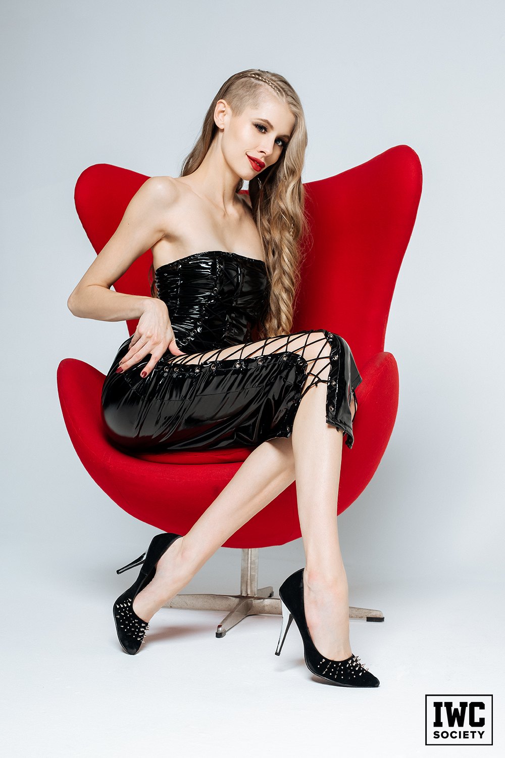 blonde dominatrix with long legs sitting in a red chair wearing a black vinyl dress
