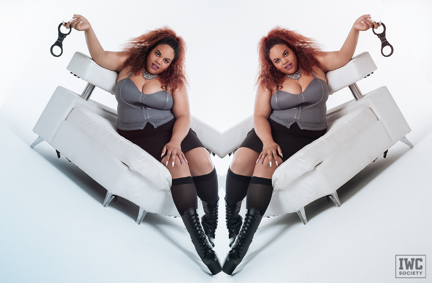 bbw femdom Ms Charmness posing on a modern white chair with black handcuffs