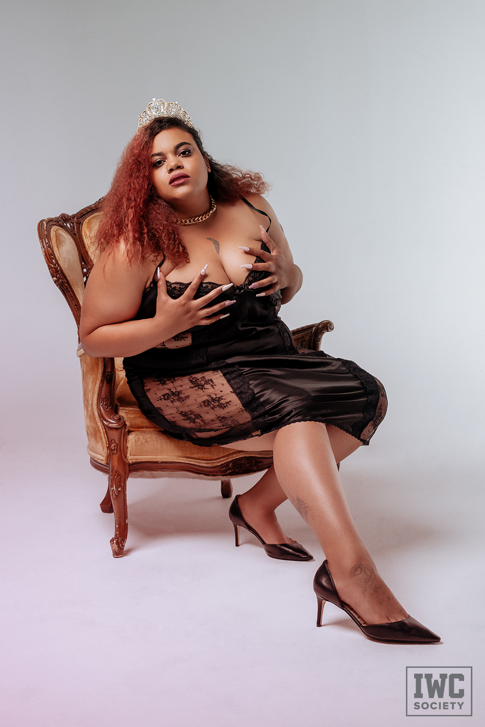 black dominatrix Ms Charmness wearing a tiara and grabbing her cleavage in a satin nightgown