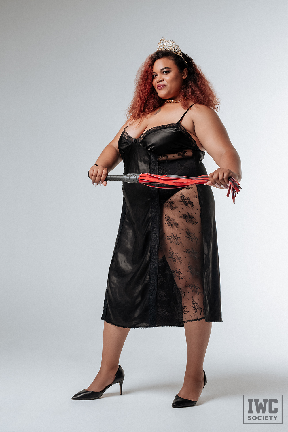 bbw femdom Ms Charmness in a black nightie and tiara holding a red flogger