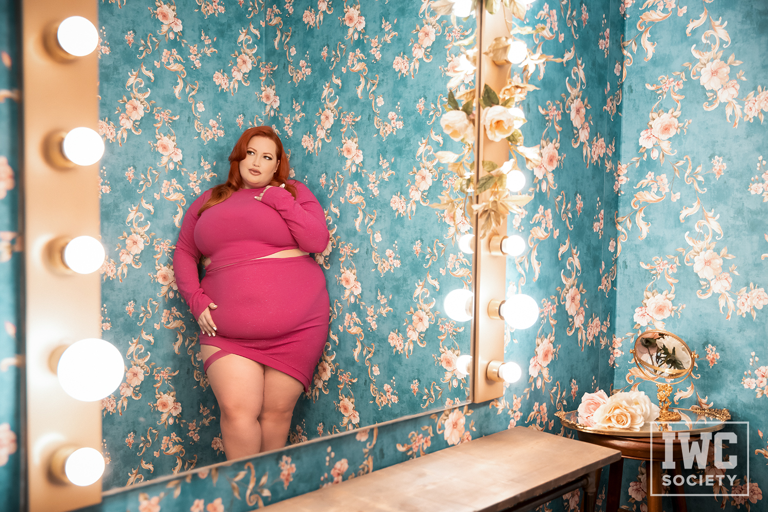 Eliza Allure BBW redhead staring into mirror while leaning on wall