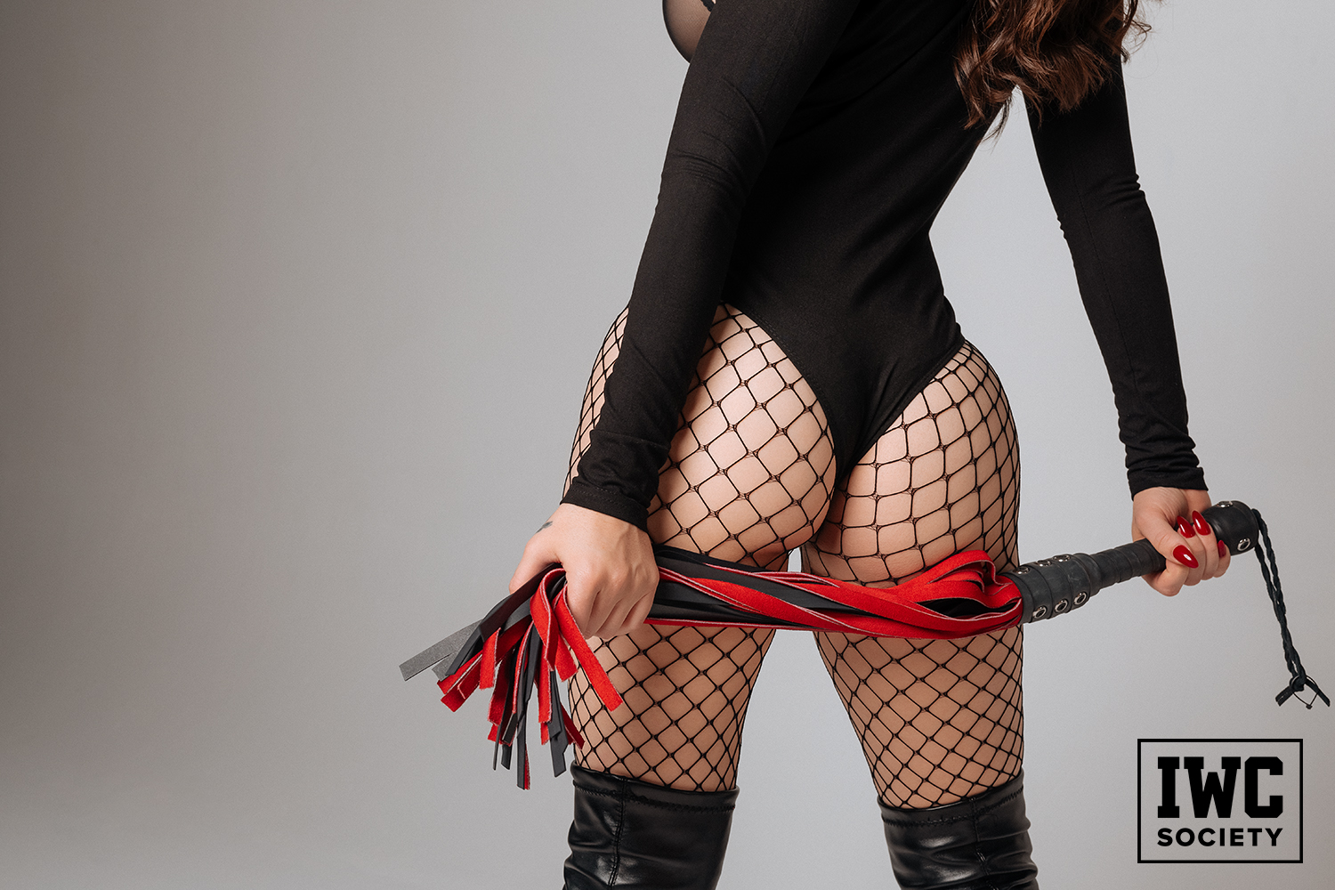 Black thong bodysuit and thigh high leather boots holding red and black whip under butt cheeks