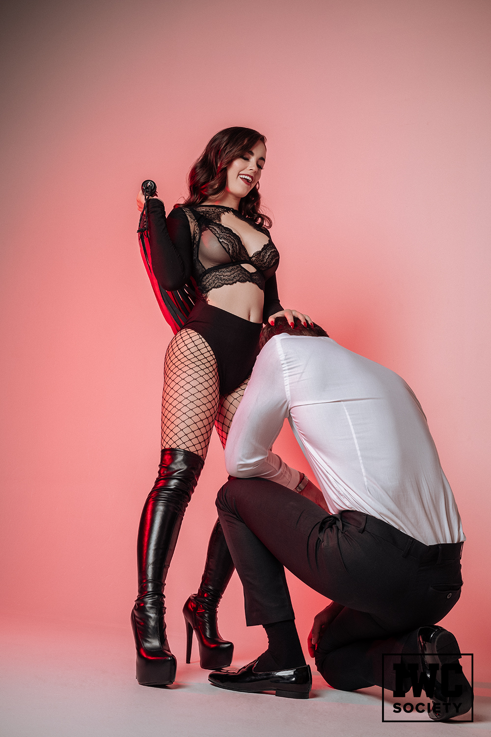 Princess in revealing black mesh bralette and high heel boots forcing man on his knees with whip in hand