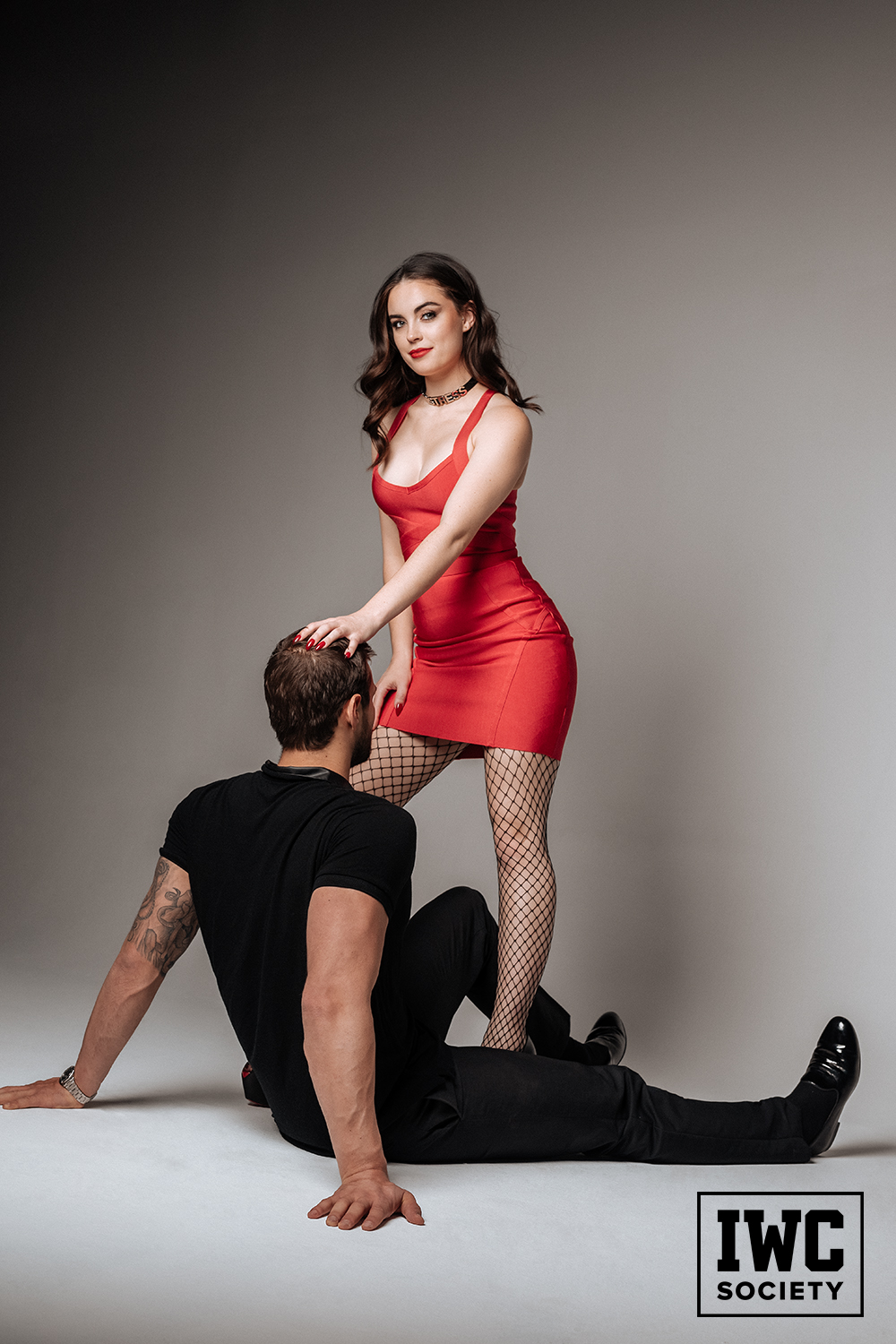 Cute Princess Camryn in red dress and stockings pushing man's head on floor to worship her legs