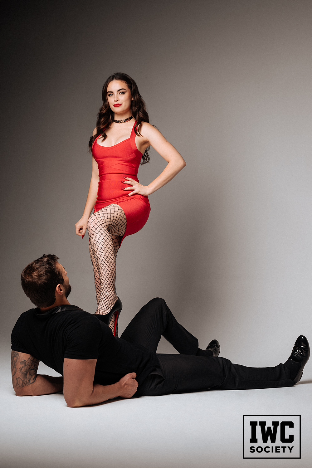 Brunette dominatrix Camryn stepping on mans chest with red sole heels and smirking