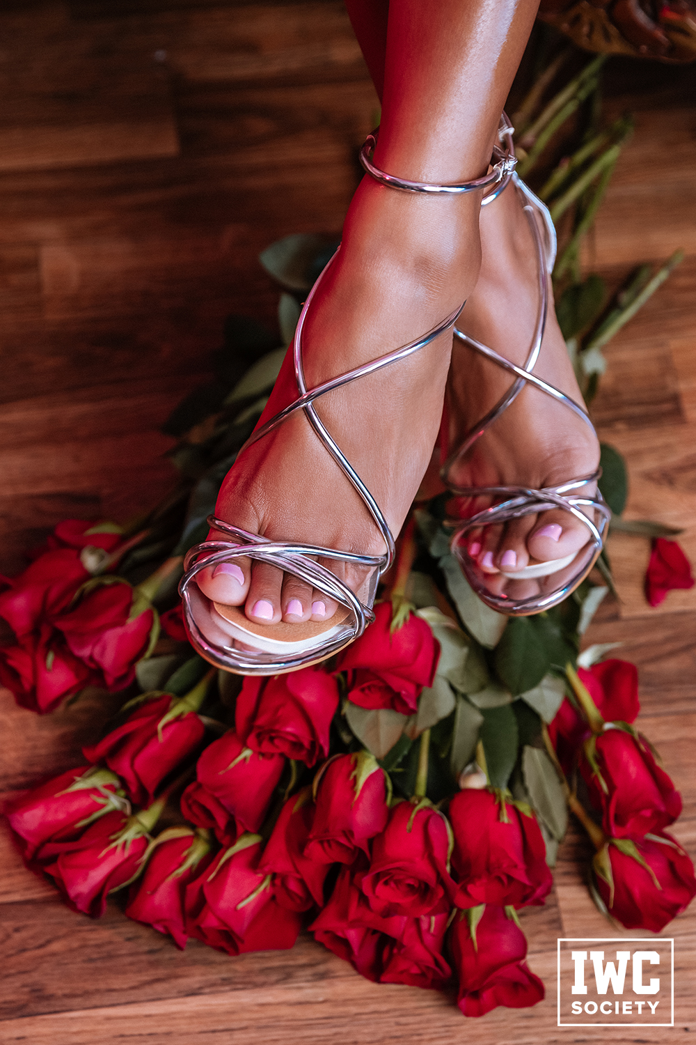 Women's feet stepping on roses with ankles crossed in sandals
