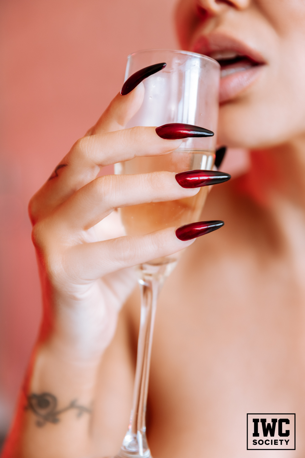 Romi Rain sipping champagne with long red fingernails