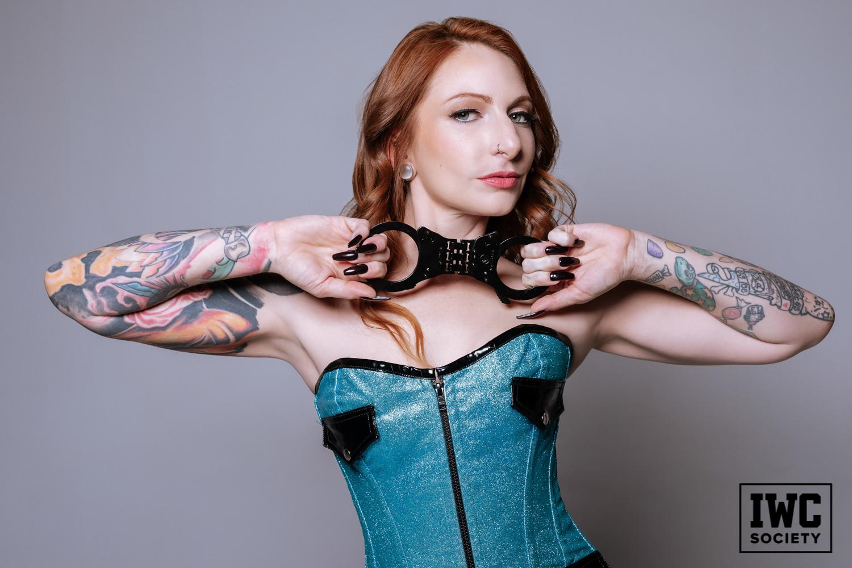 Goddess Olivia Rose redhead femdom holding black handcuffs