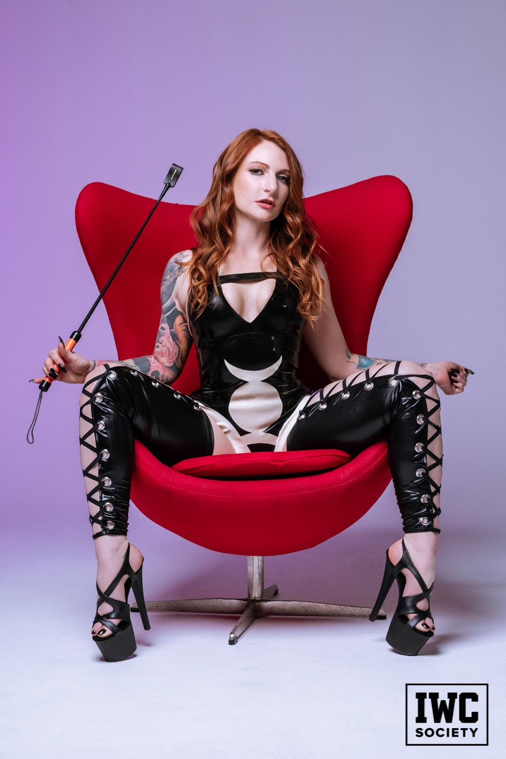 tattooed dominatrix in red chair and latex in black heels