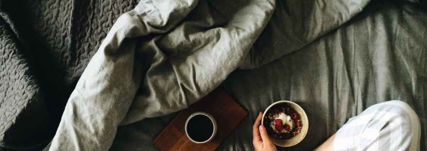 crop woman with breakfast in bed