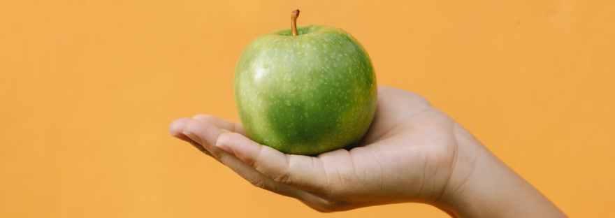 fresh apple on hand of woman