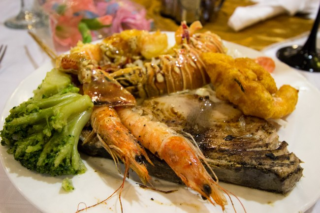 Dinner plate consisting of grilled fish, prawns, lobster, and broccoli