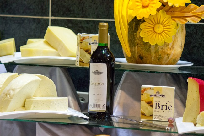 An assortment of cheeses, including brie cheese, and a bottle of red wine.