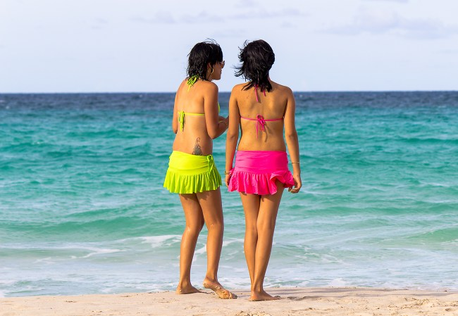 Two girls walking down the beach in bright lime and pink beach wear