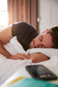 Man Asleep In Bed With Mobile Phone On Bedside Table