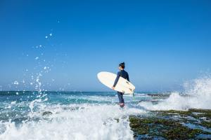 Surfer with surfboard at seaside