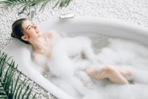 Attractive lady lying in bath with foam, top view