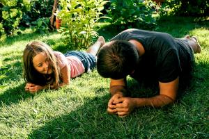 Daughter and father doing planking exercise on grass in garden. Family sport concept