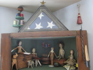 """The little wooden dolls have taken over the """"attic""""of the corner cupboard as their sewing room."""
