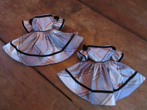 A pair of silk plaid dresses cut on the bias with velvet ribbon trim <3