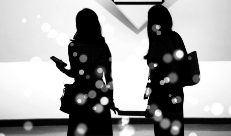 Two women holding cellphones