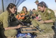 A női katonák a backgammont játszanak. A katonák kikapcsolódnak a katonai kiképzés során. Nő izraeli katona játszik a gitár a háttérben.