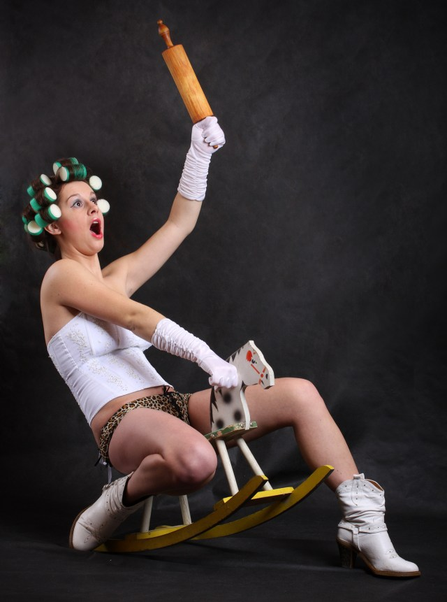 Screaming militant feminist with rolling pin ridden on a wooden
