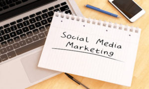 """Picture of a laptop and a notepad stating """"social media marketing"""""""