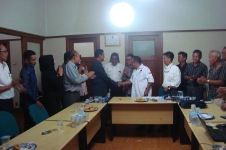 Ketua DPW Partai NasDem Jabar Eka Santosa (tengah-baju putih) bersalaman dengan Ketua DPD Partai Hanura Jabar Azhar Aung usai menjalin kesepakatan berkoalisi di DPRD Jabar 2014-2019. (JABARTODAY/AVILA DWIPUTRA)