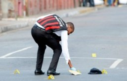 A policeman places markers at a crime scene on Delamere Avenue, St Andrew - Image via jamaica-gleaner.com