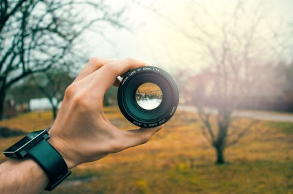 Man holding a camera lens up to look through.