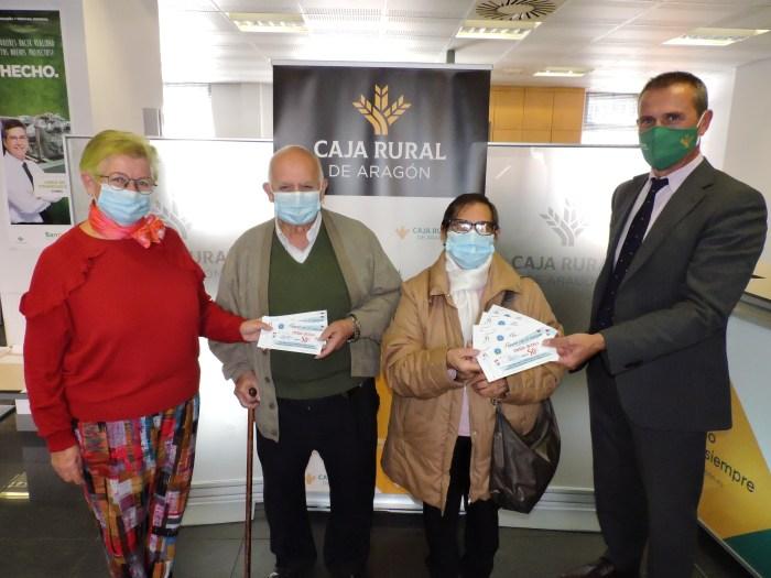 En la imagen, Lyn Briggs, presidenta de la organización empresarial, y Fernando Baratech, director de la Oficina de Caja Rural de Aragón de Sabiñánigo entregando los cheques de la campaña Compra con el corazón a los ganadores. (FOTO: AEPAG)