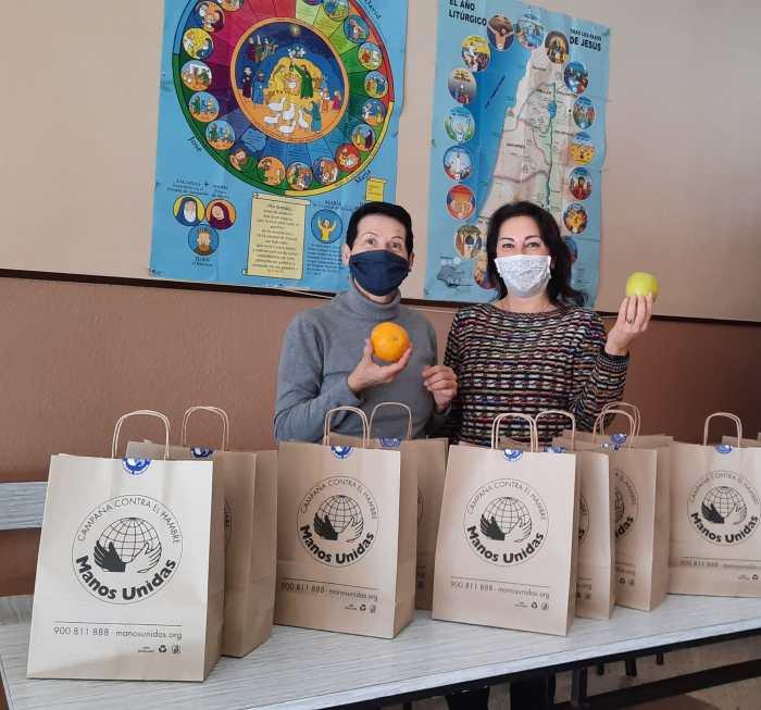 Las voluntarias de Manos Unidas, junto a las bolsas solidarias de la campaña.