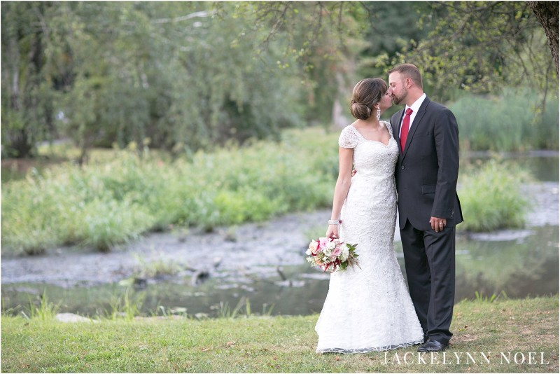 Leila and Matt kissing with the lake and willow trees in the background.
