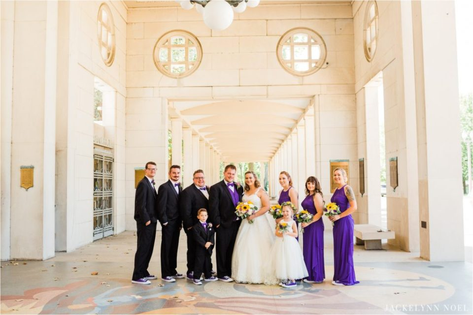 Dan and Lisa's wedding party poses in the hall of The Muny of Forest Park wearing wedding colors of purple and white