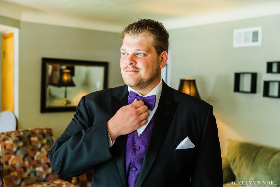 Dan adjusting his tie while wearing his tux